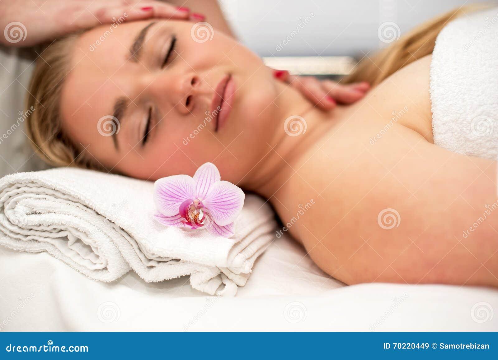 Jonge vrouw die op massagelijst liggen die gezichtsmassage ontvangen beaut
