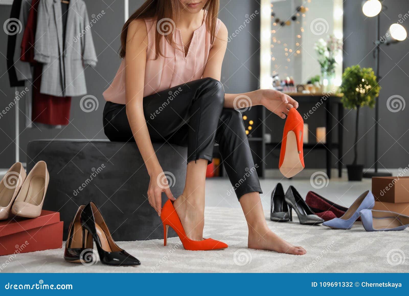 Jonge vrouw die op schoenen probeert