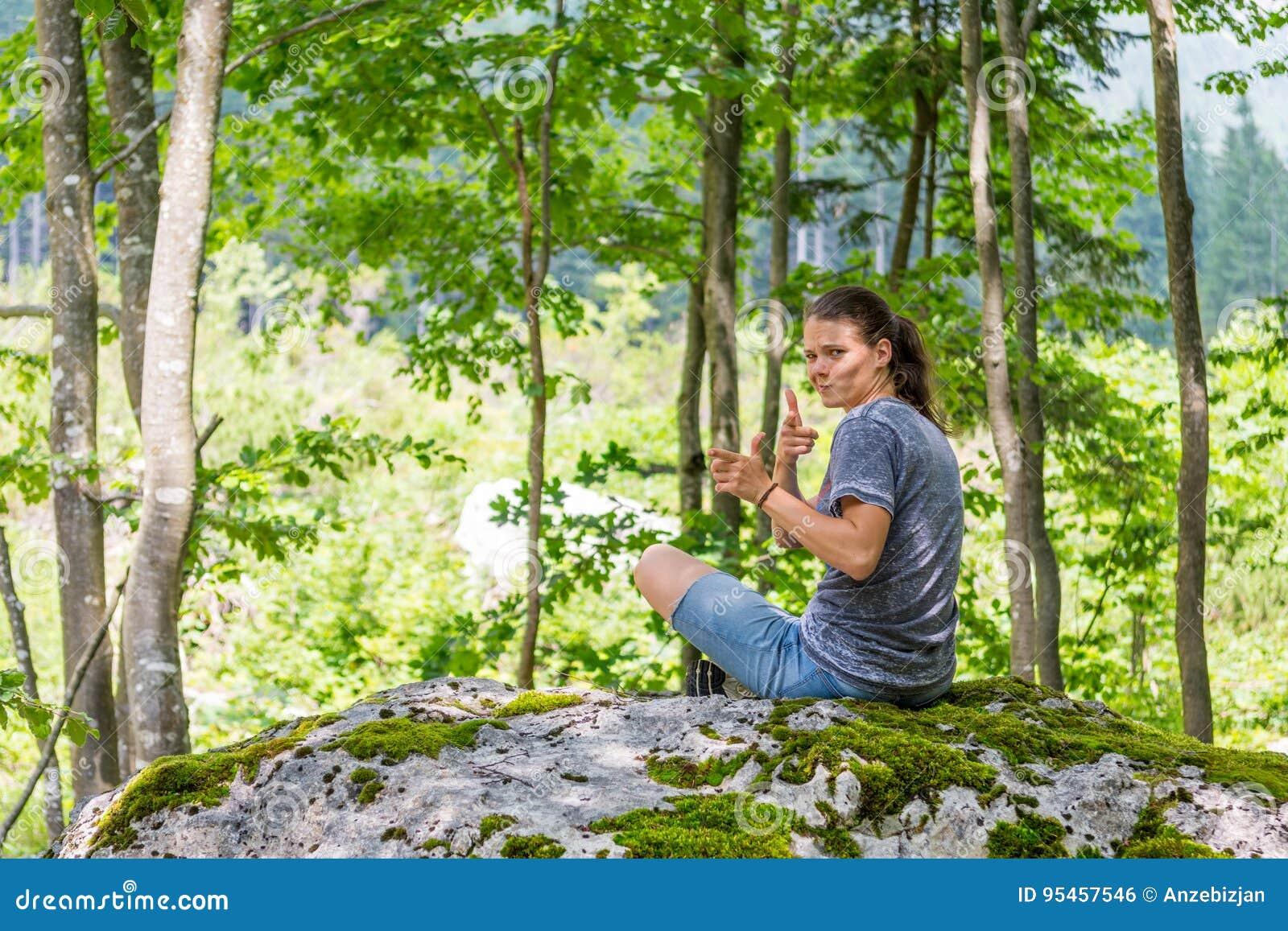 Jonge vrouw die over haar schouder op een bosrots kijken