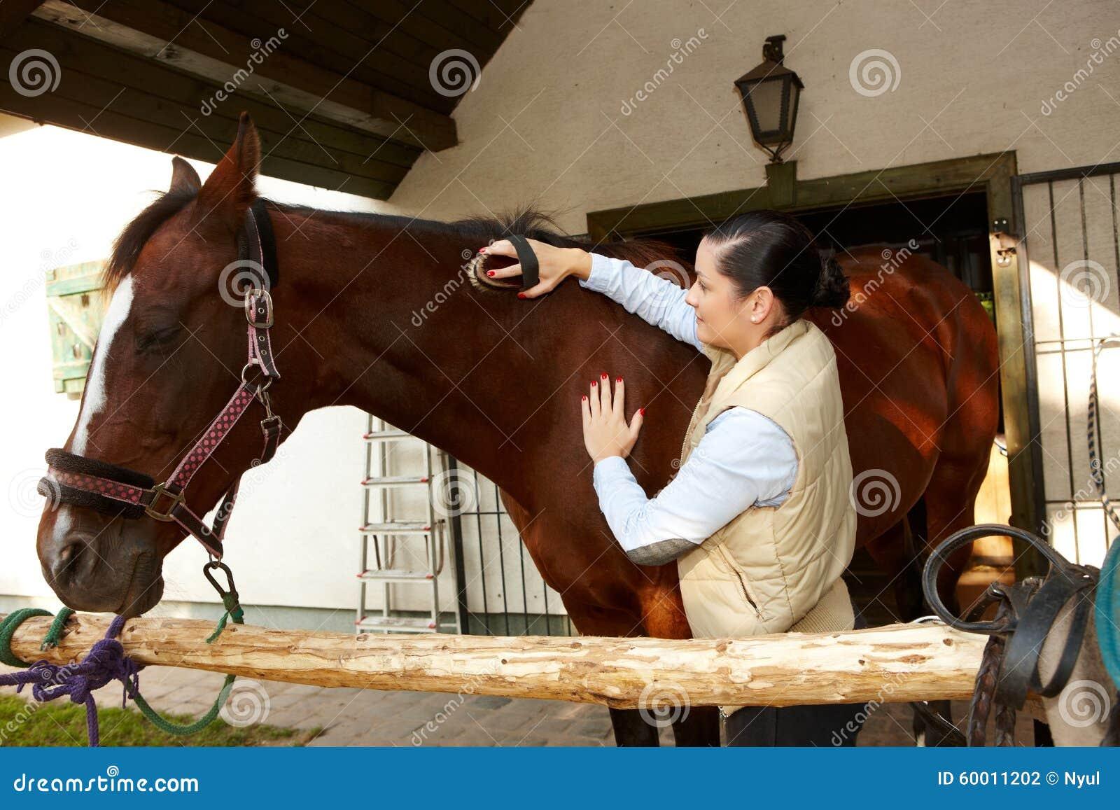 Jonge vrouw die paard strelen