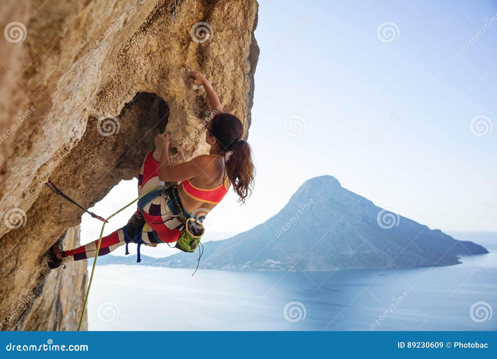 Jonge vrouw die richel op klip worstelen te beklimmen