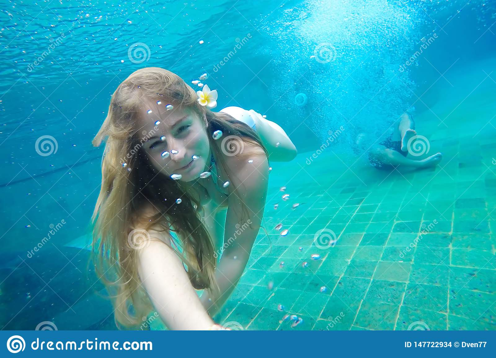Jonge vrouw die selfie onder water in de pool maken In haar is het haar een frangipanibloem Tegen de achtergrond jonge kerel gesp