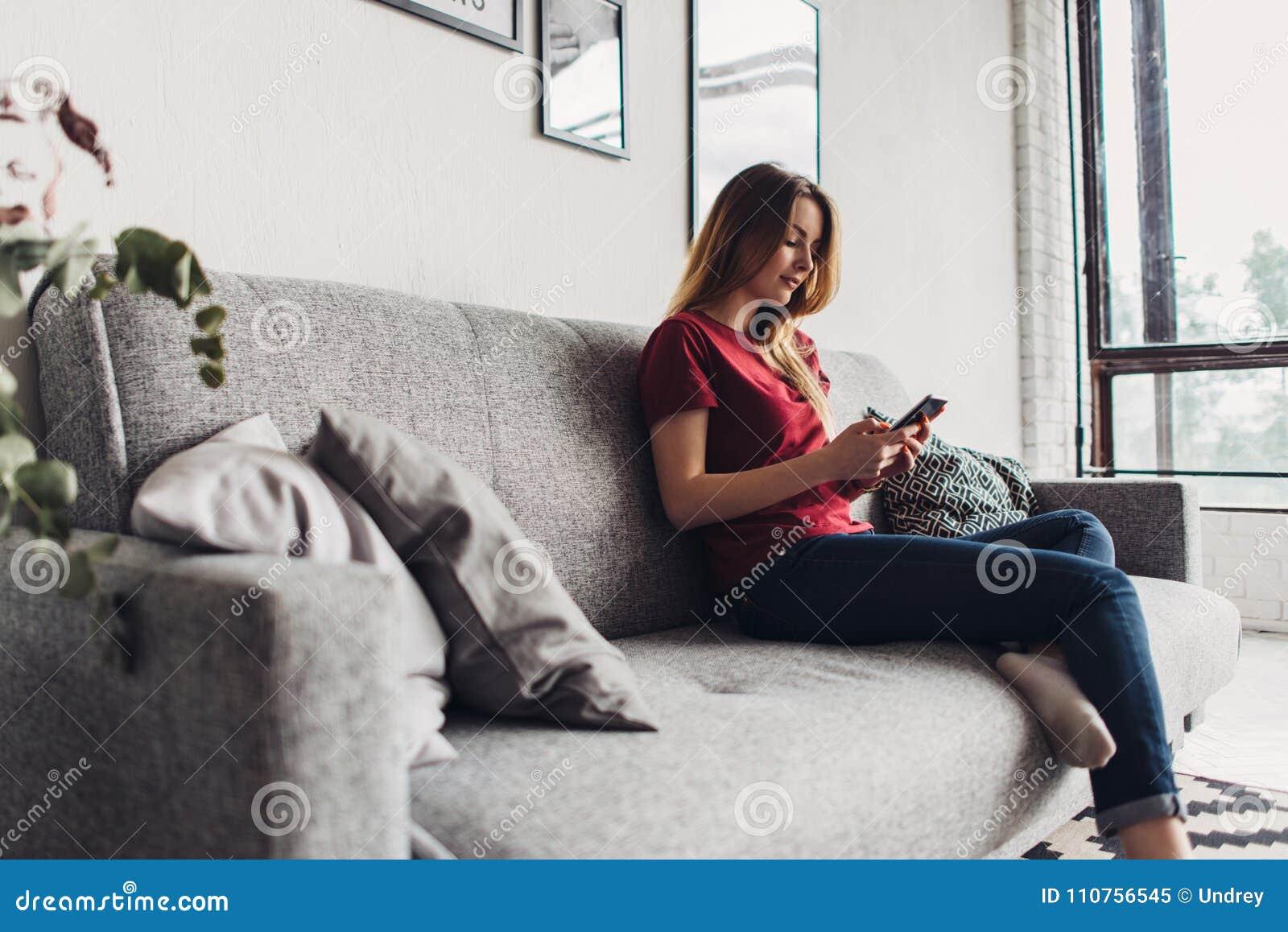 Jonge vrouw die slimme telefoon met behulp van terwijl het ontspannen op laag bij woonkamer