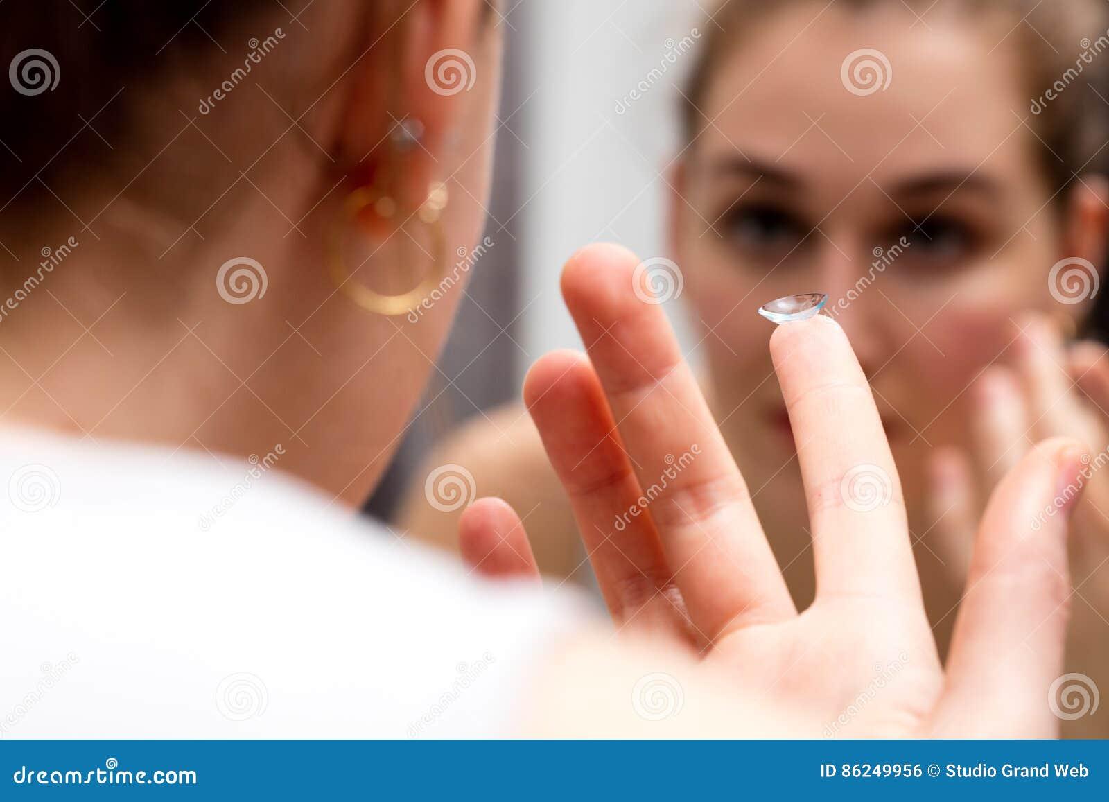 Jonge vrouw die in spiegel kijken om haar contactlens te veranderen