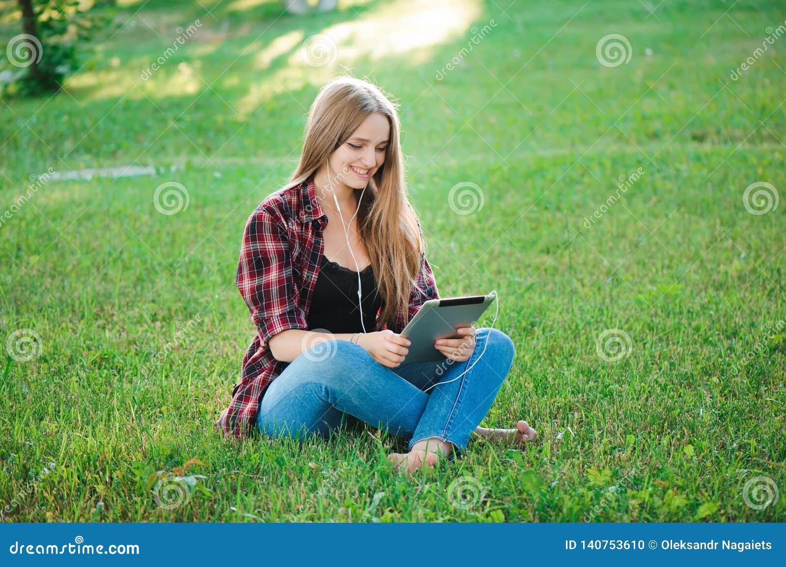 Jonge vrouw die tablet openluchtzitting op gras gebruiken, het glimlachen