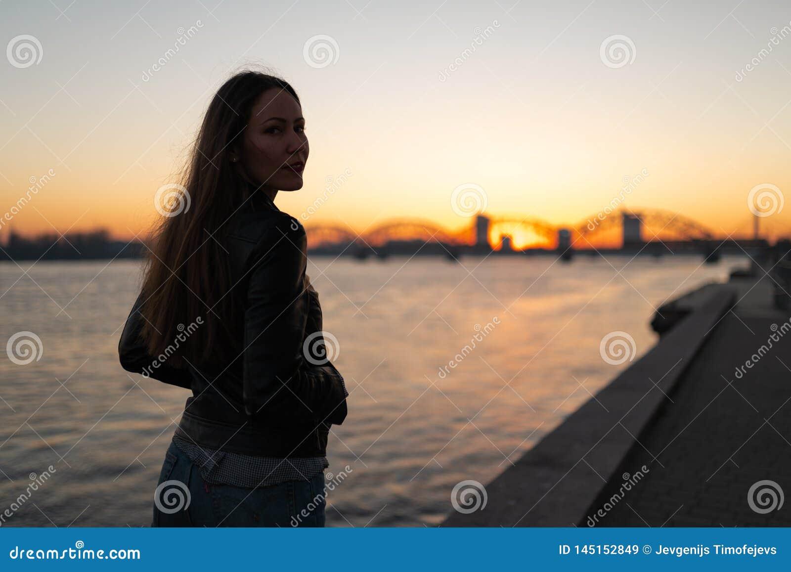 Jonge vrouw die van een zonsonderganggang langs de rivier Daugava met een mening over duidelijke blauwe hemel genieten