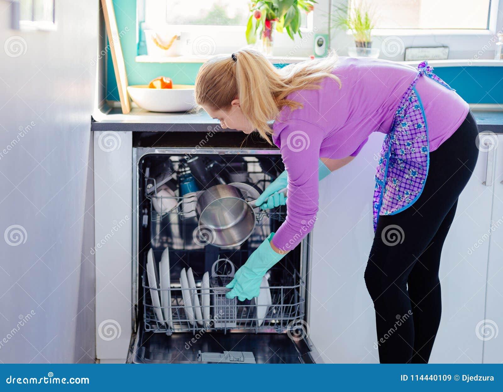 Jonge vrouw die vuile schotels zetten aan afwasmachine