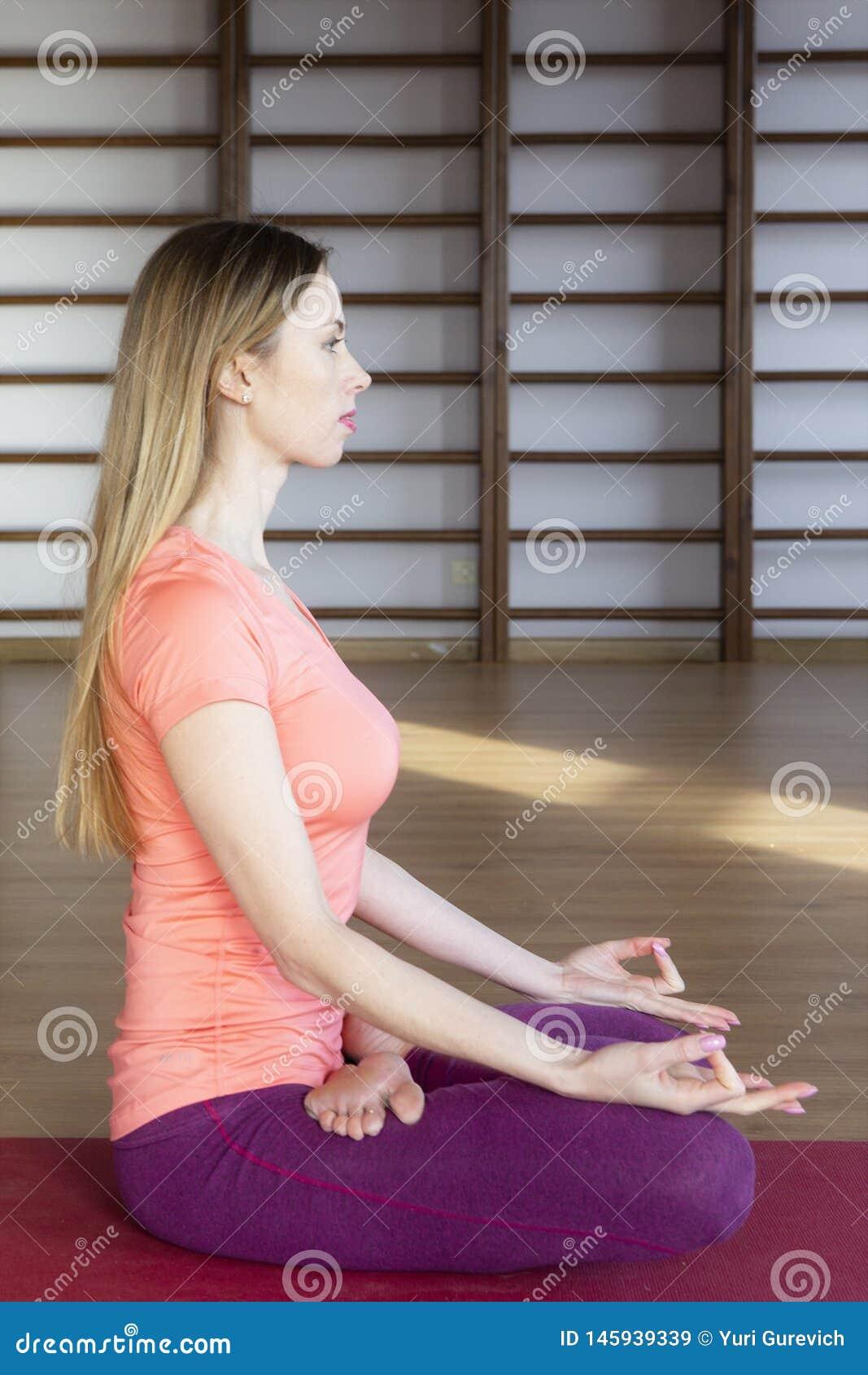 Jonge vrouw die yoga op de deken in de zaal doen