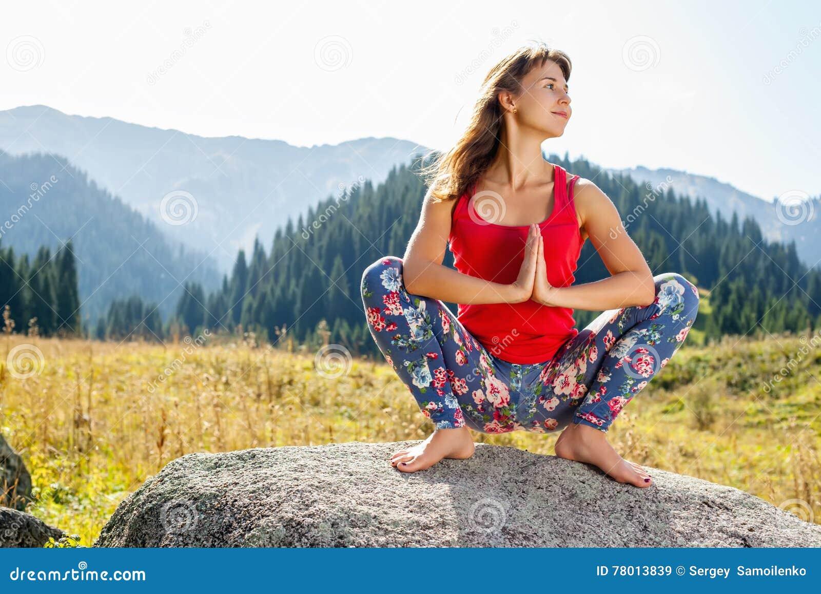 Jonge vrouw die yoga op een rots doen