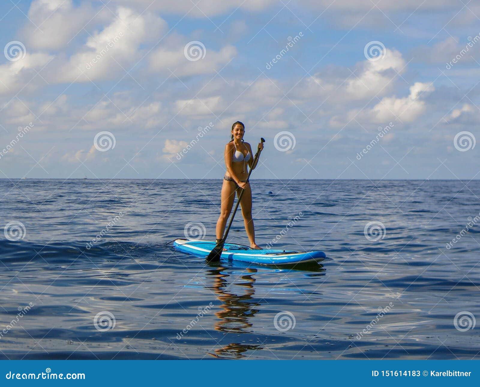 Jonge vrouw die zich op paddleboard op overzeese oppervlakte bevinden Sportenactiviteit het paddleboarding Tribune op peddel Meis