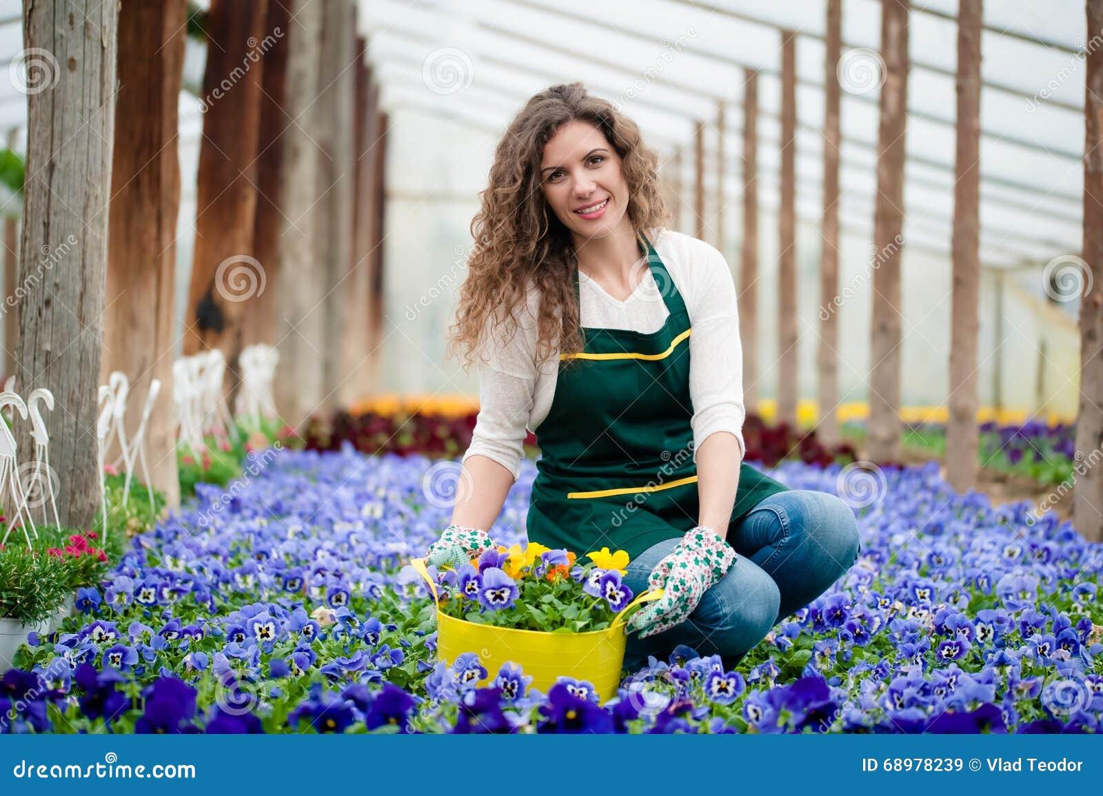 Jonge vrouw in een kleurrijke bloemtuin in een serre die een bloempot plukken