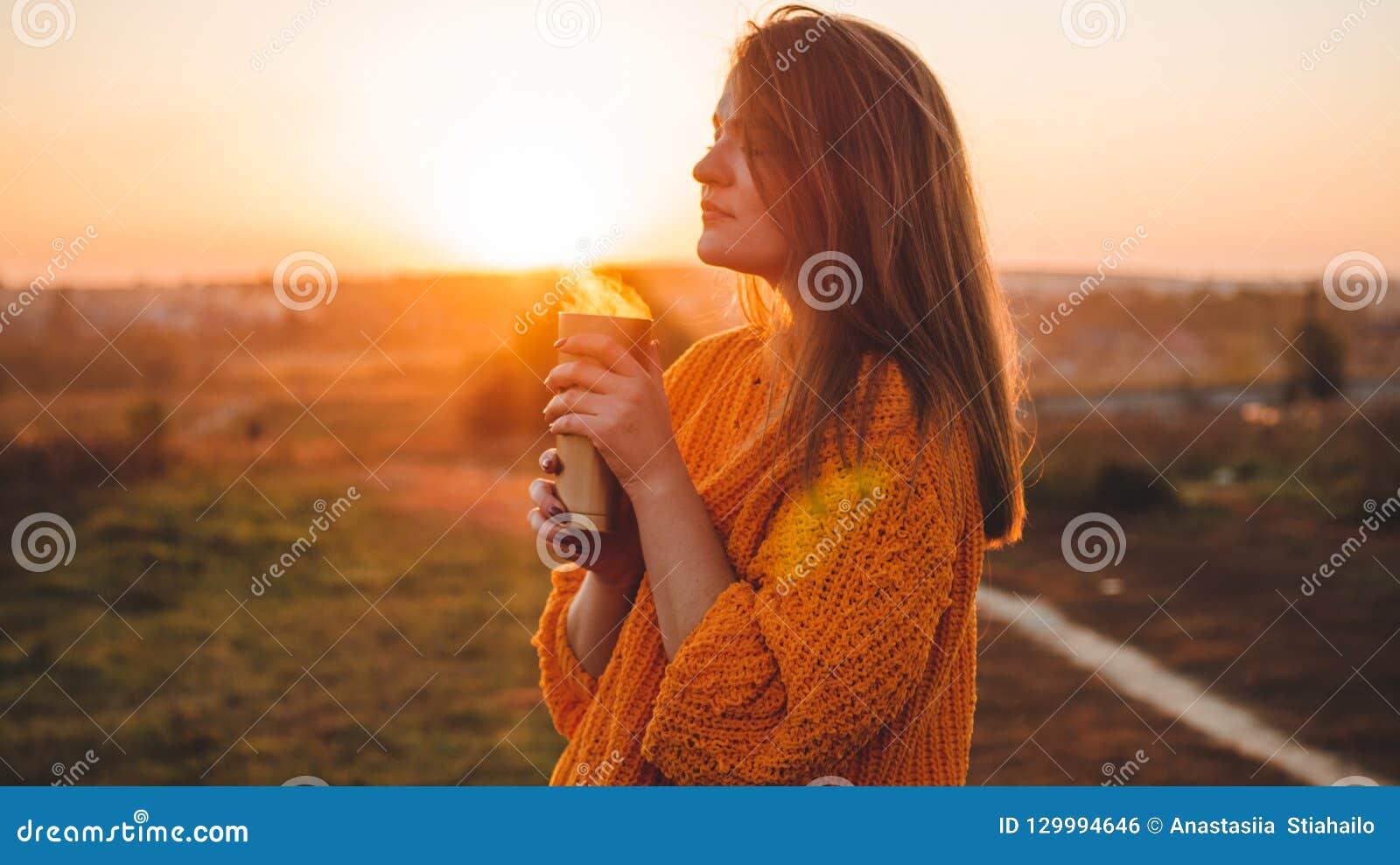 Jonge vrouw in een oranje sweater met openluchtportret van de thermosflessen het thermokop in zacht zonnig daglicht De herfst Zon