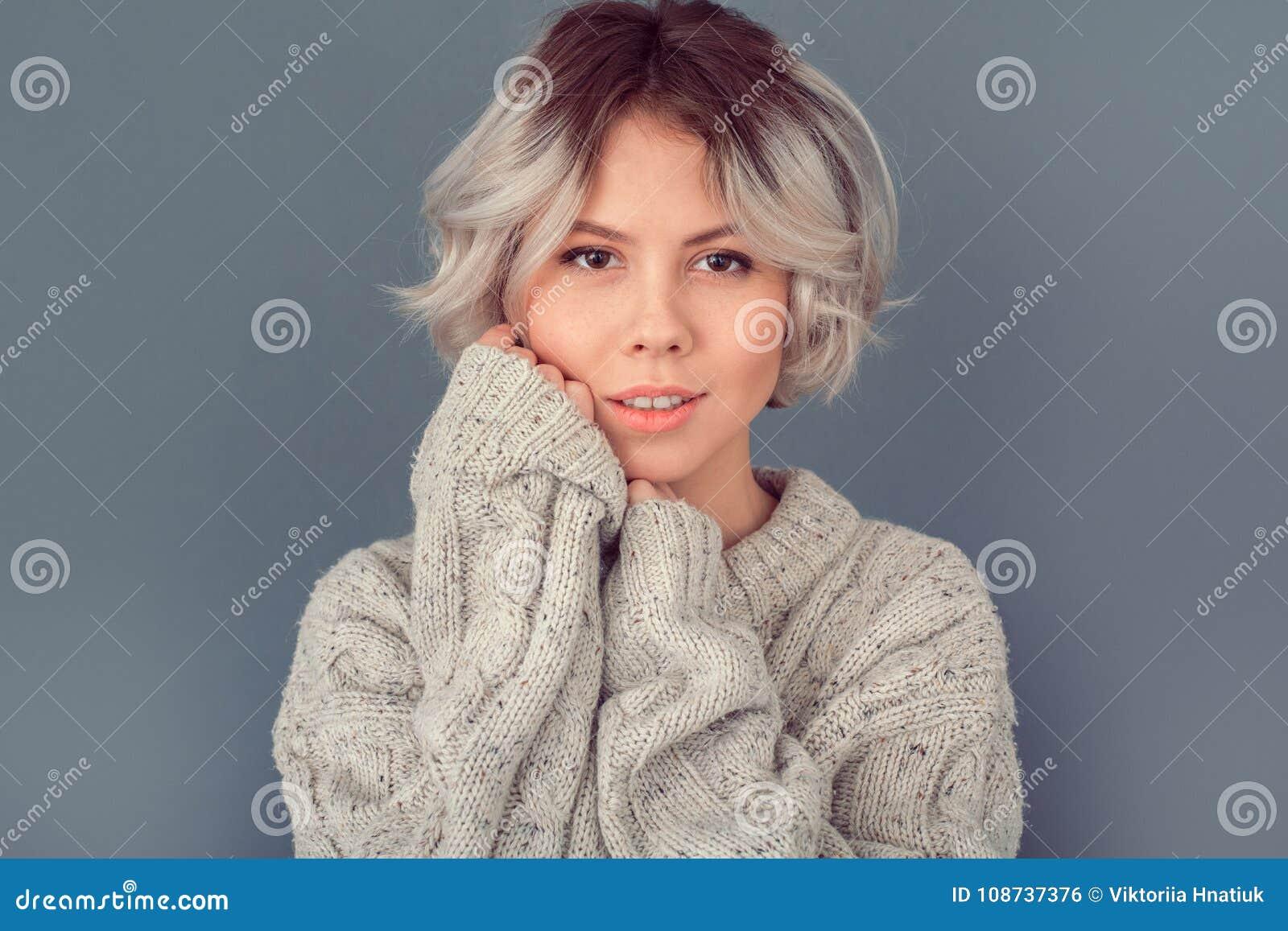 Jonge vrouw in een wollen die sweater op grijze het conceptenmanier van de muurwinter wordt geïsoleerd