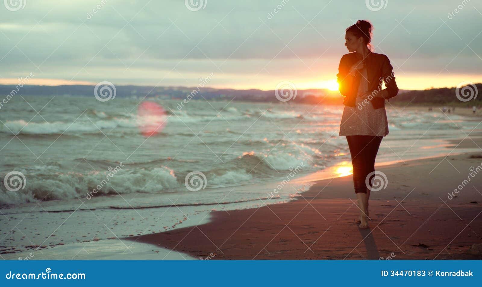Jonge vrouw en de zonsondergang op de achtergrond