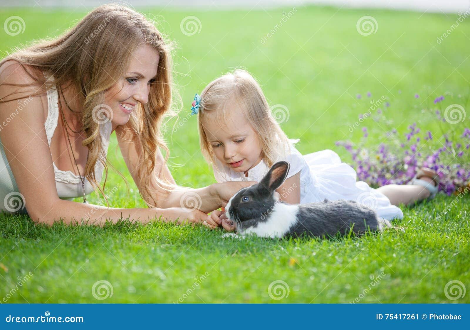 Jonge vrouw en haar dochter die met een huisdierenkonijn spelen