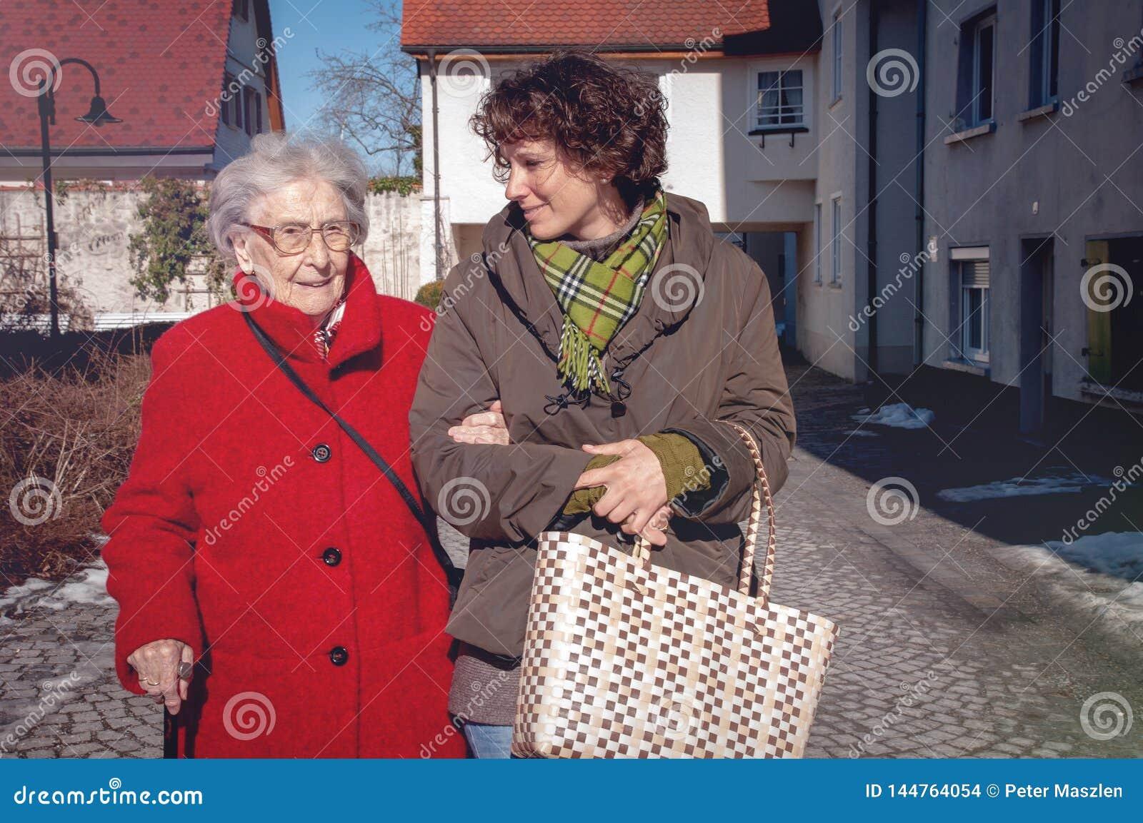 Jonge vrouw en hogere vrouw die voor het winkelen gaan