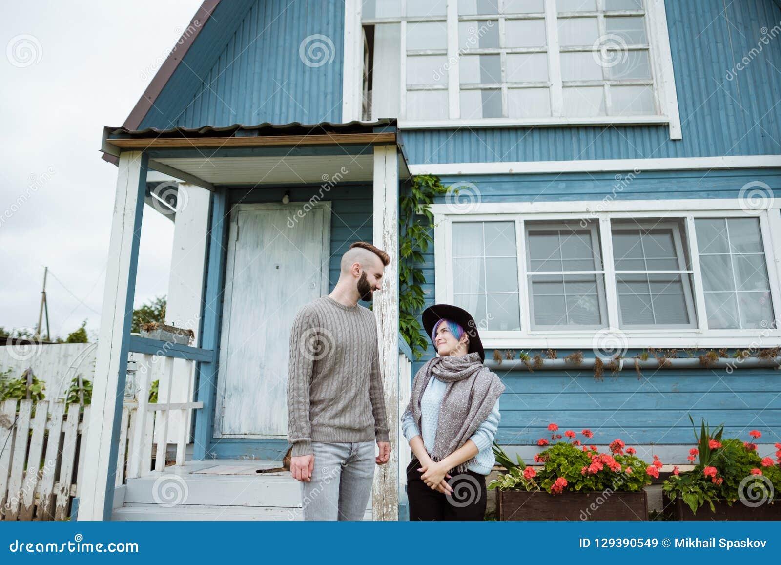 Jonge vrouw en man, familie, die op portiek van dorpshuis zitten met pompoenen