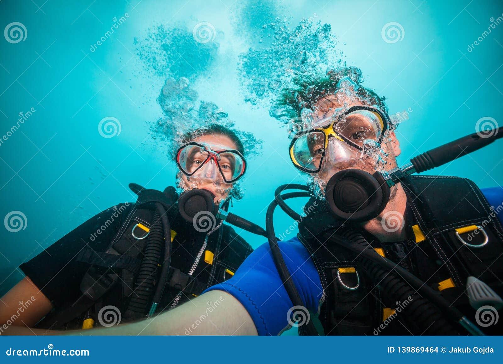 Jonge vrouw en man scuba-duikers die selfie maken