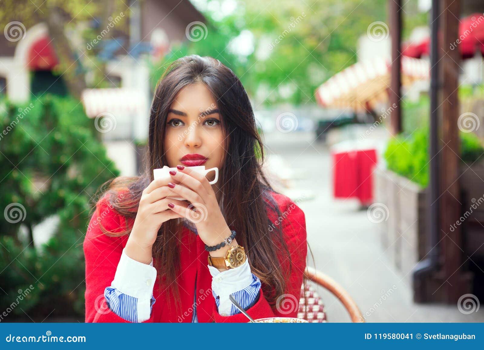 Jonge vrouw het denken holdingskoffie op een in koffieterras
