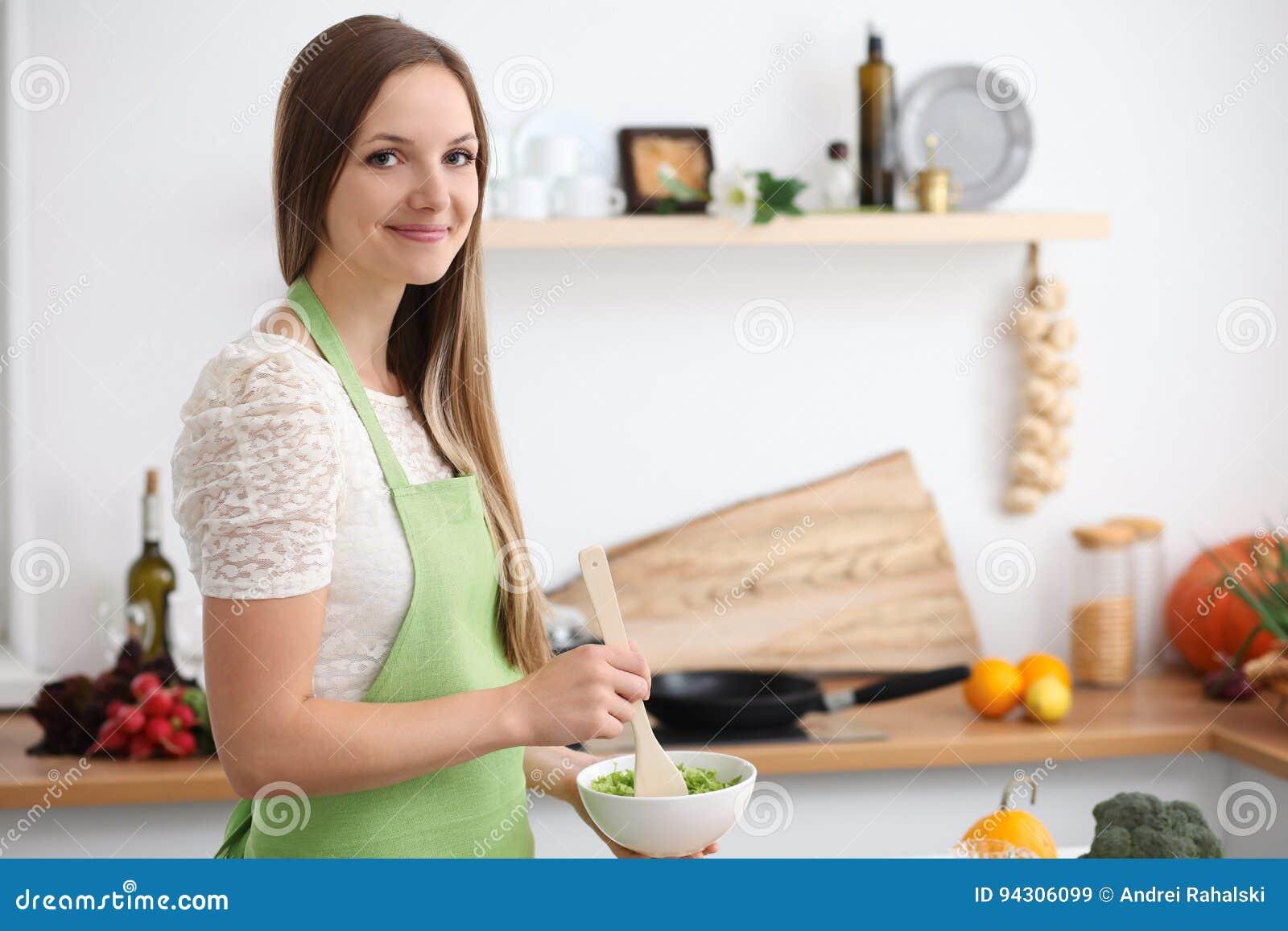 Jonge vrouw in het groene schort koken in de keuken Huisvrouw die verse salade snijden