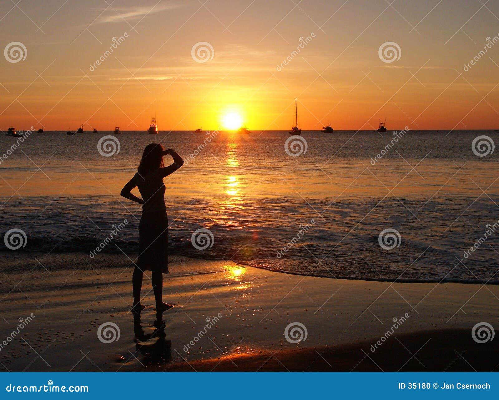 Jonge vrouw het letten op zonsondergang