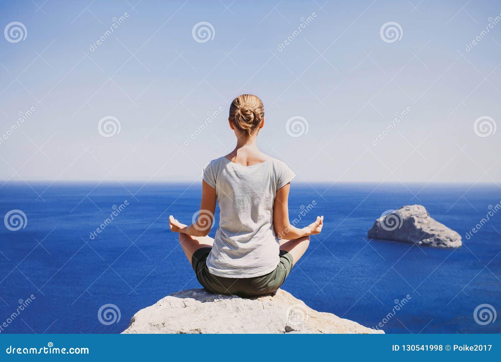 Jonge vrouw het praktizeren yoga dichtbij het overzees