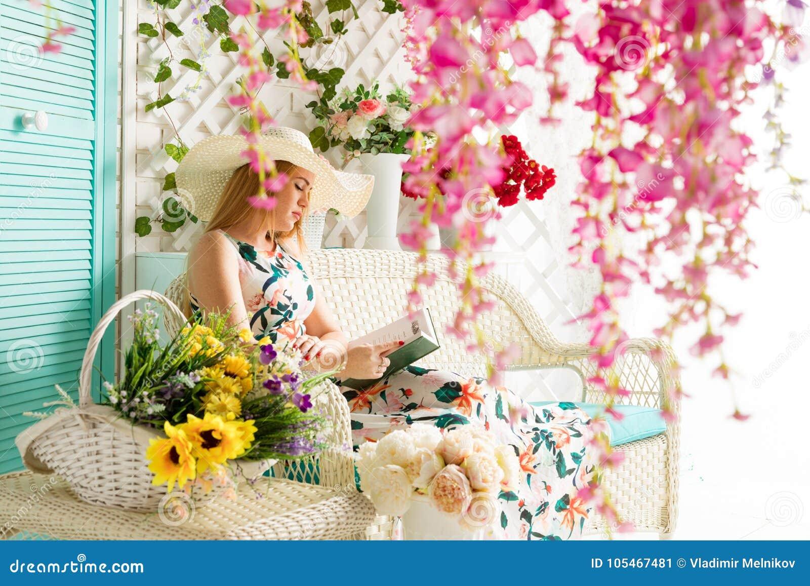 Jonge vrouw met boek in de zomerterras
