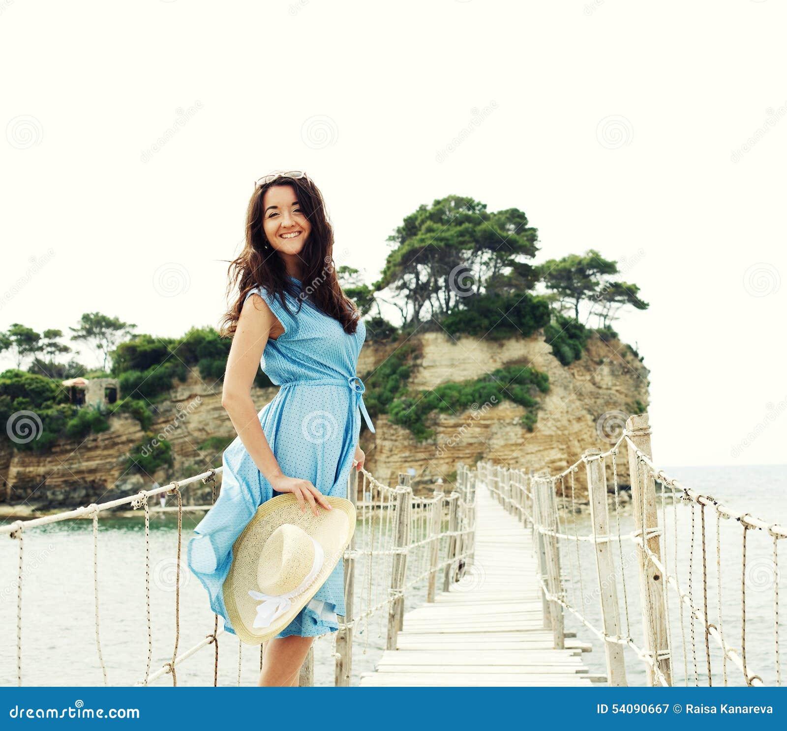 Jonge vrouw met de zomerhoed het stellen op de brug