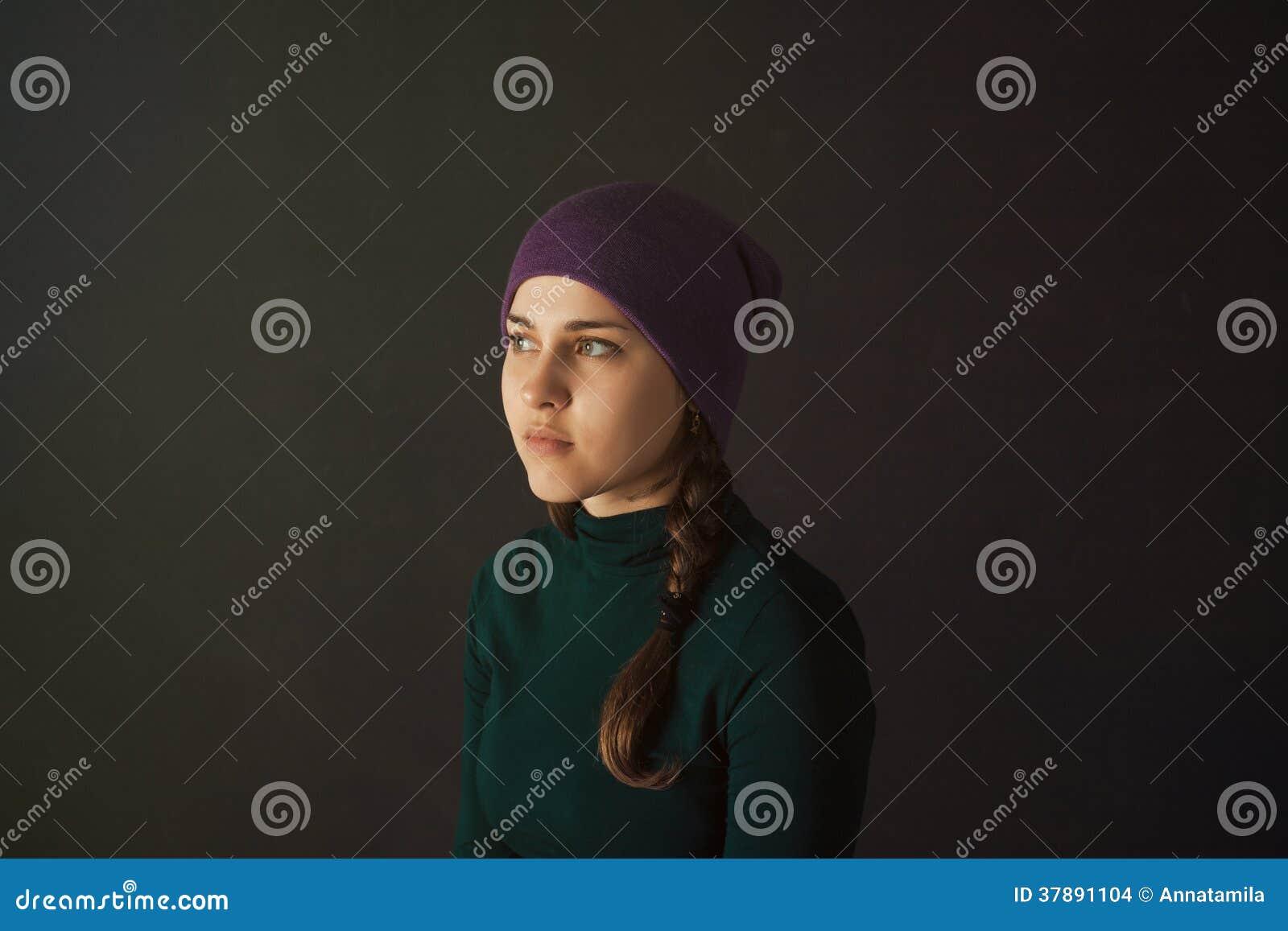 Jonge vrouw met een hoed op een donkere achtergrond