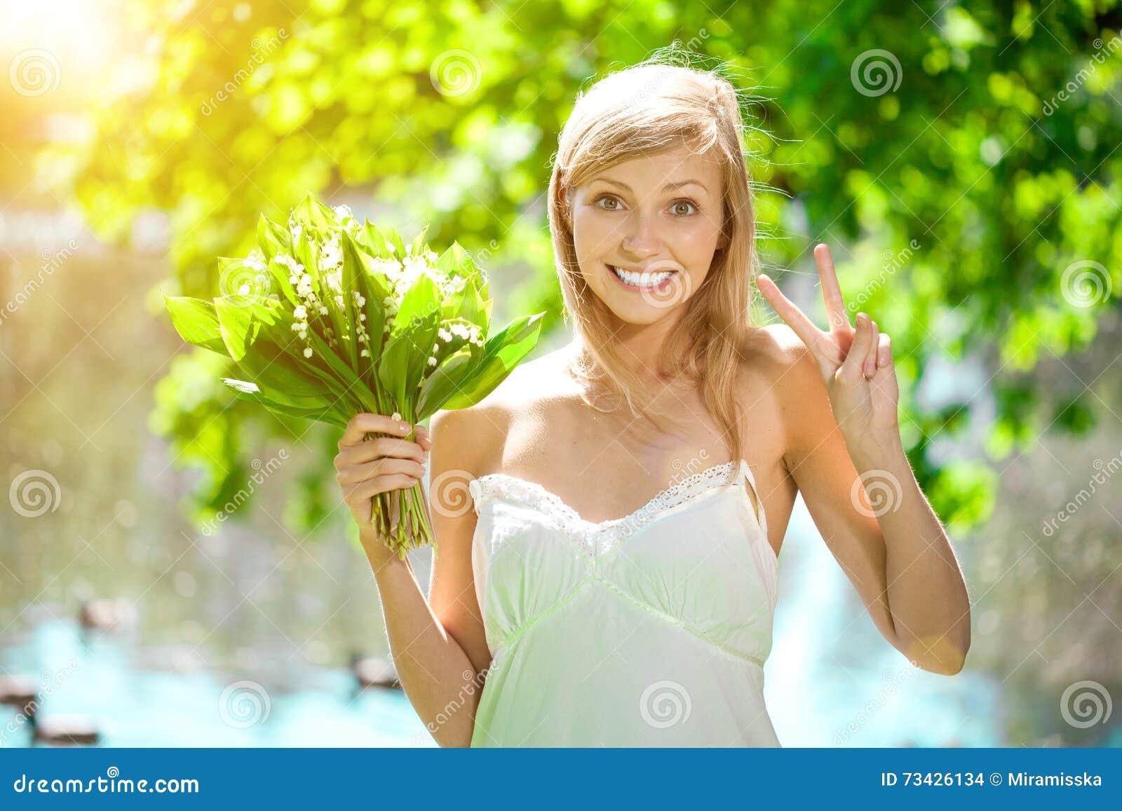 Jonge vrouw met een mooie glimlach met gezonde tanden met flowe