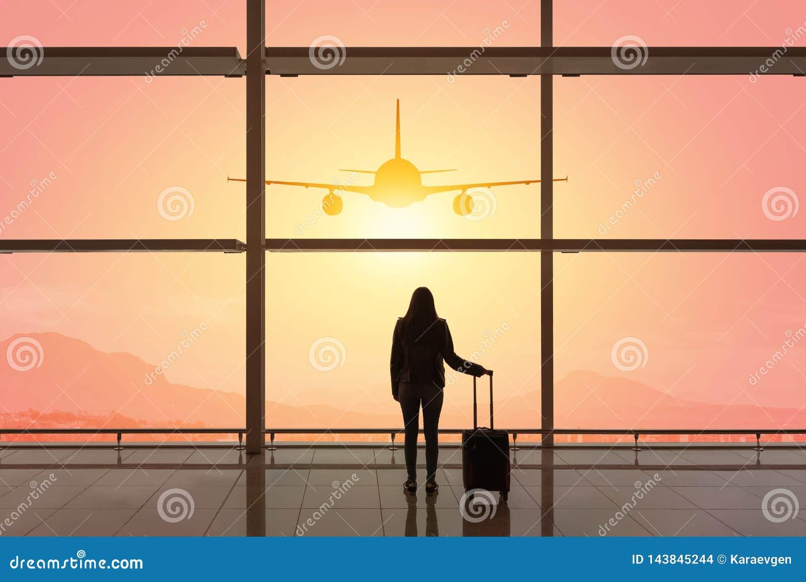 Jonge vrouw met koffer in de vertrekzaal bij luchthaven reis concept