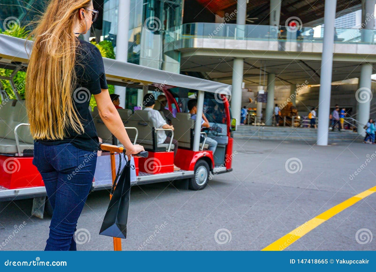 Jonge vrouw met lange haren op elektrische autoped Het meisje op de elektrische autoped drinkt koffie