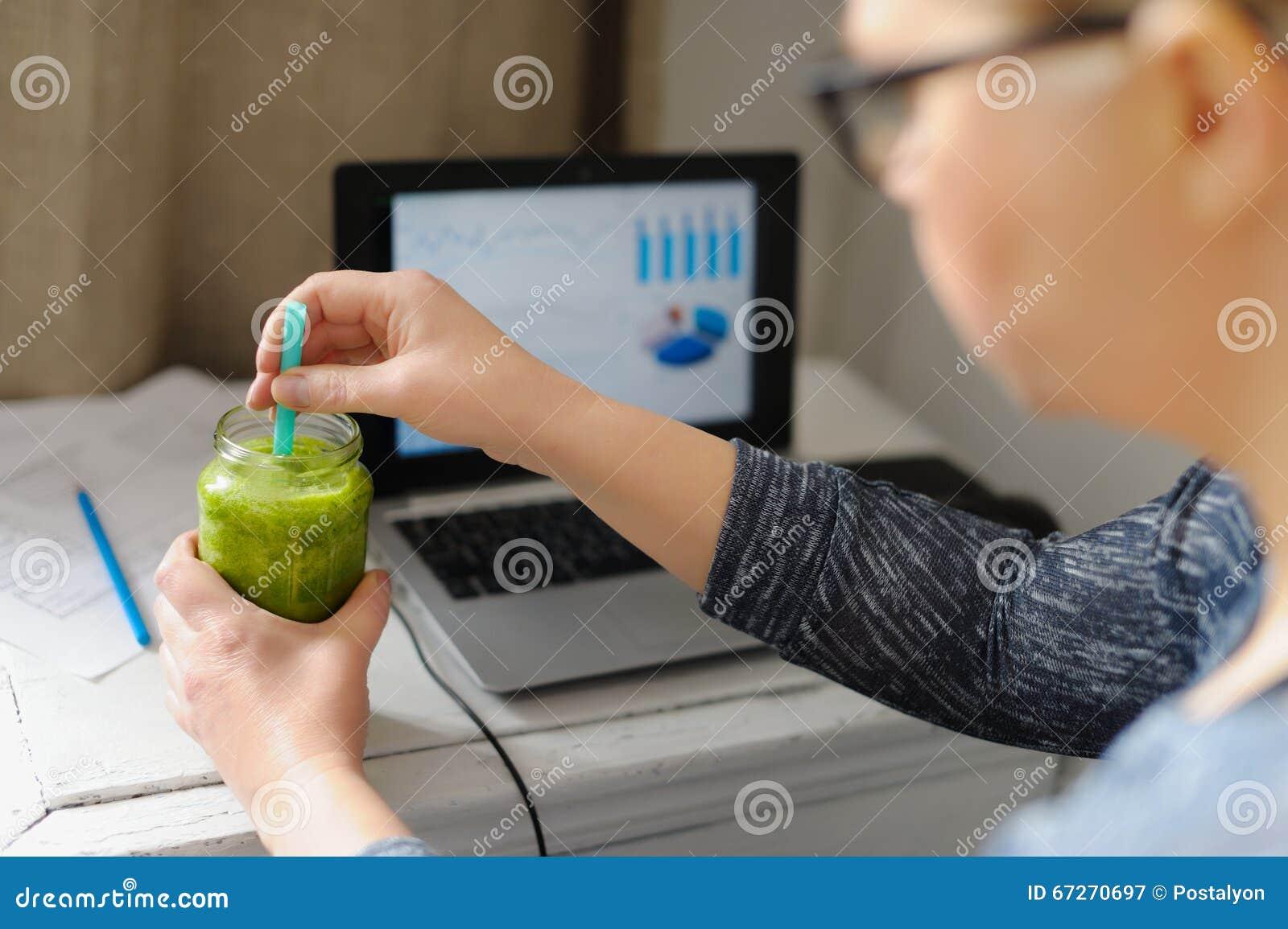 Jonge vrouw met laptop bij houten lijst Drinkende groene smoothie