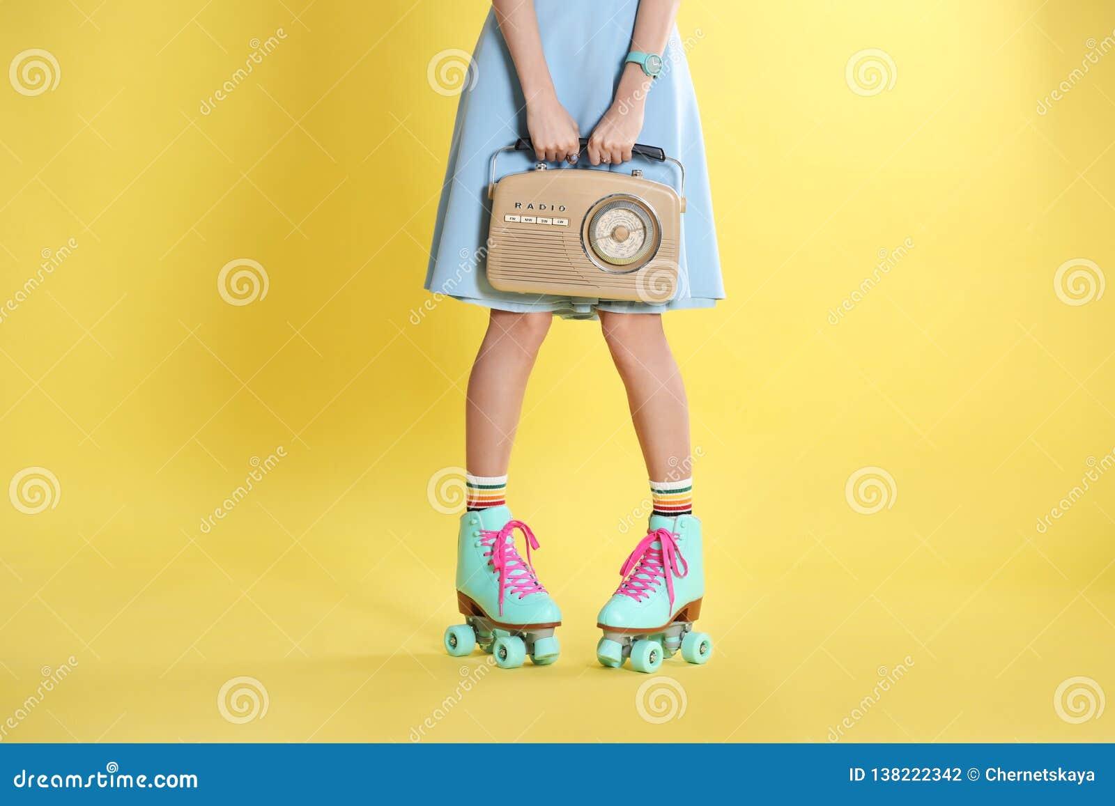 Jonge vrouw met rolschaatsen en retro radio op kleurenachtergrond
