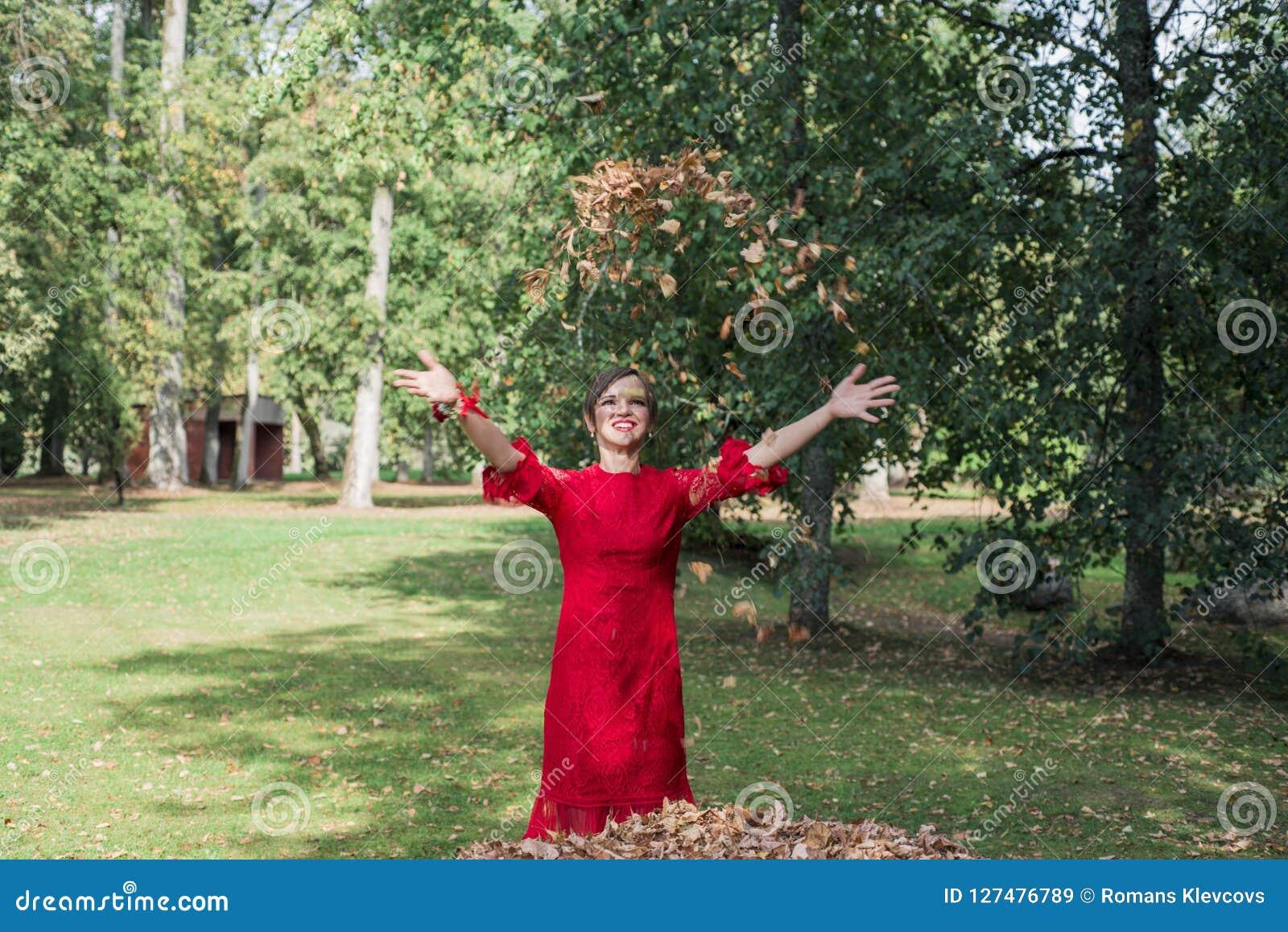 Jonge vrouw in rode kleding Werp omhoog de de herfstbladeren