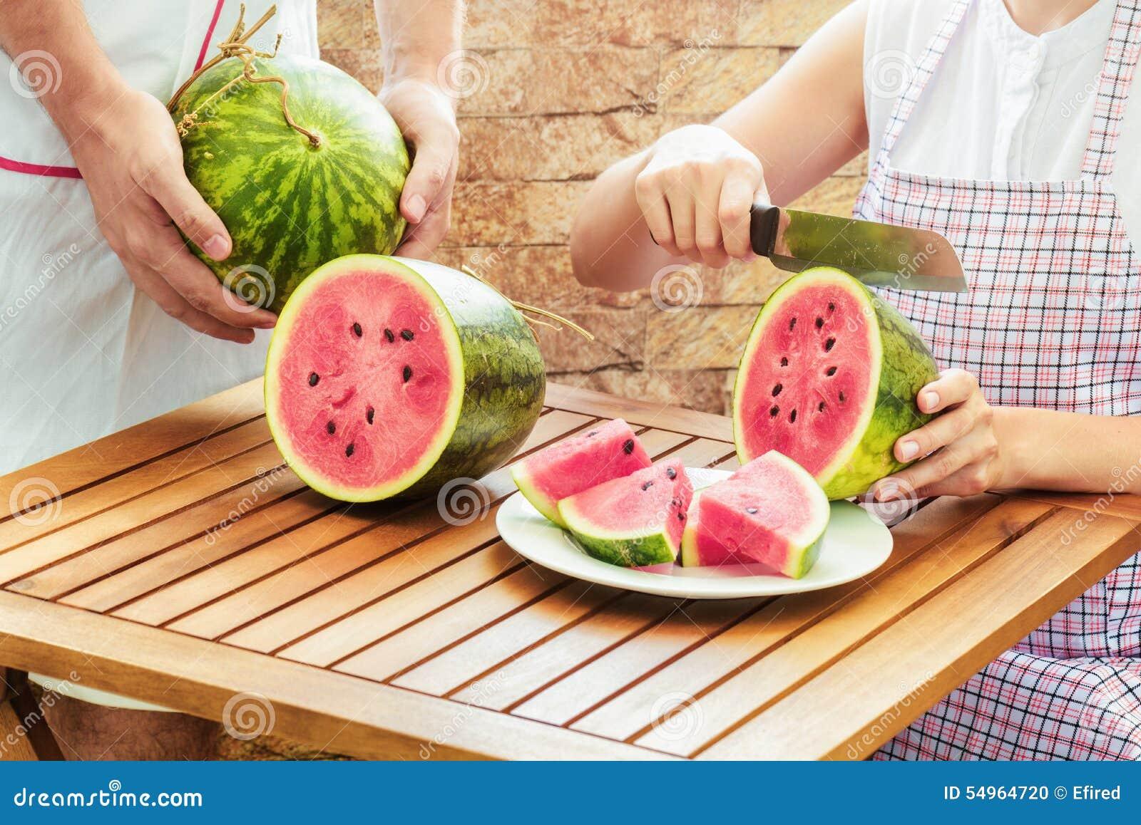 Jonge vrouw in schort die verse rijpe sappige watermeloen snijden