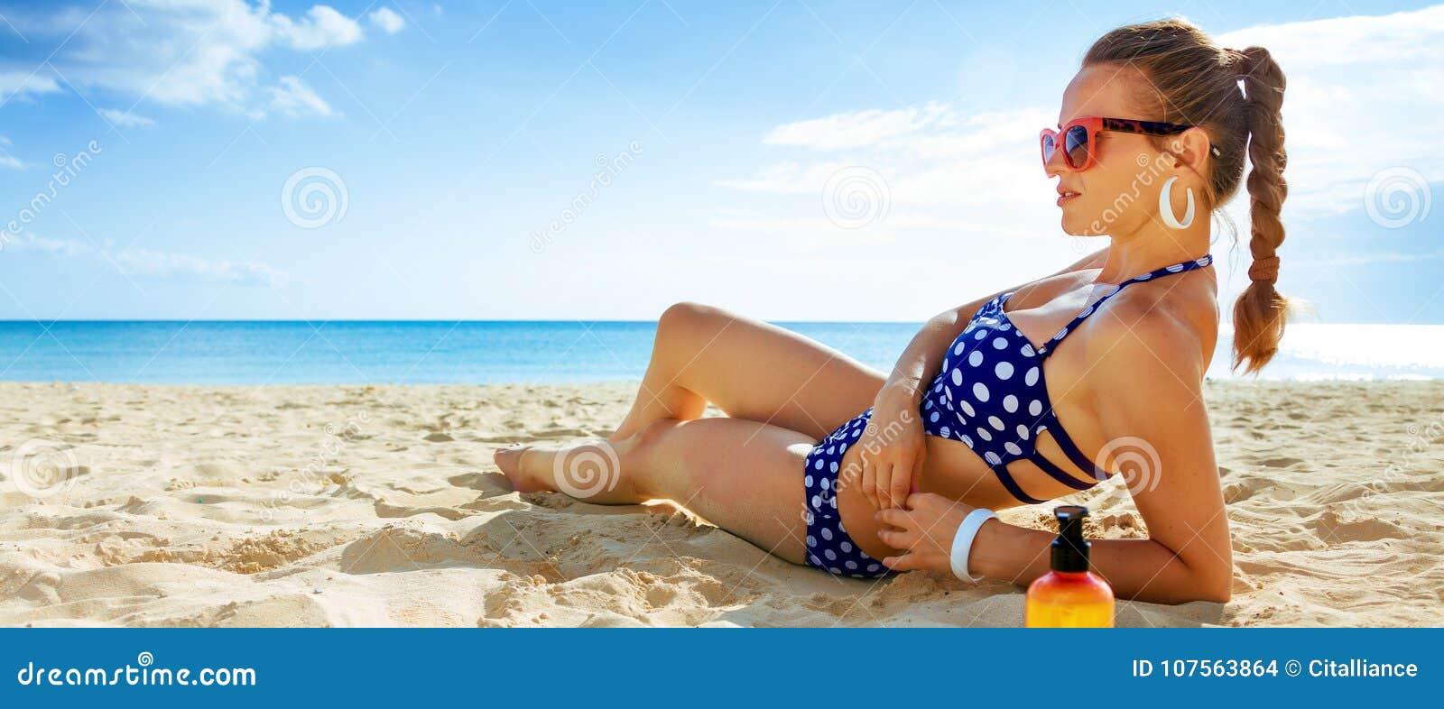 Jonge vrouw in swimwear bij zeekust het zonnebaden