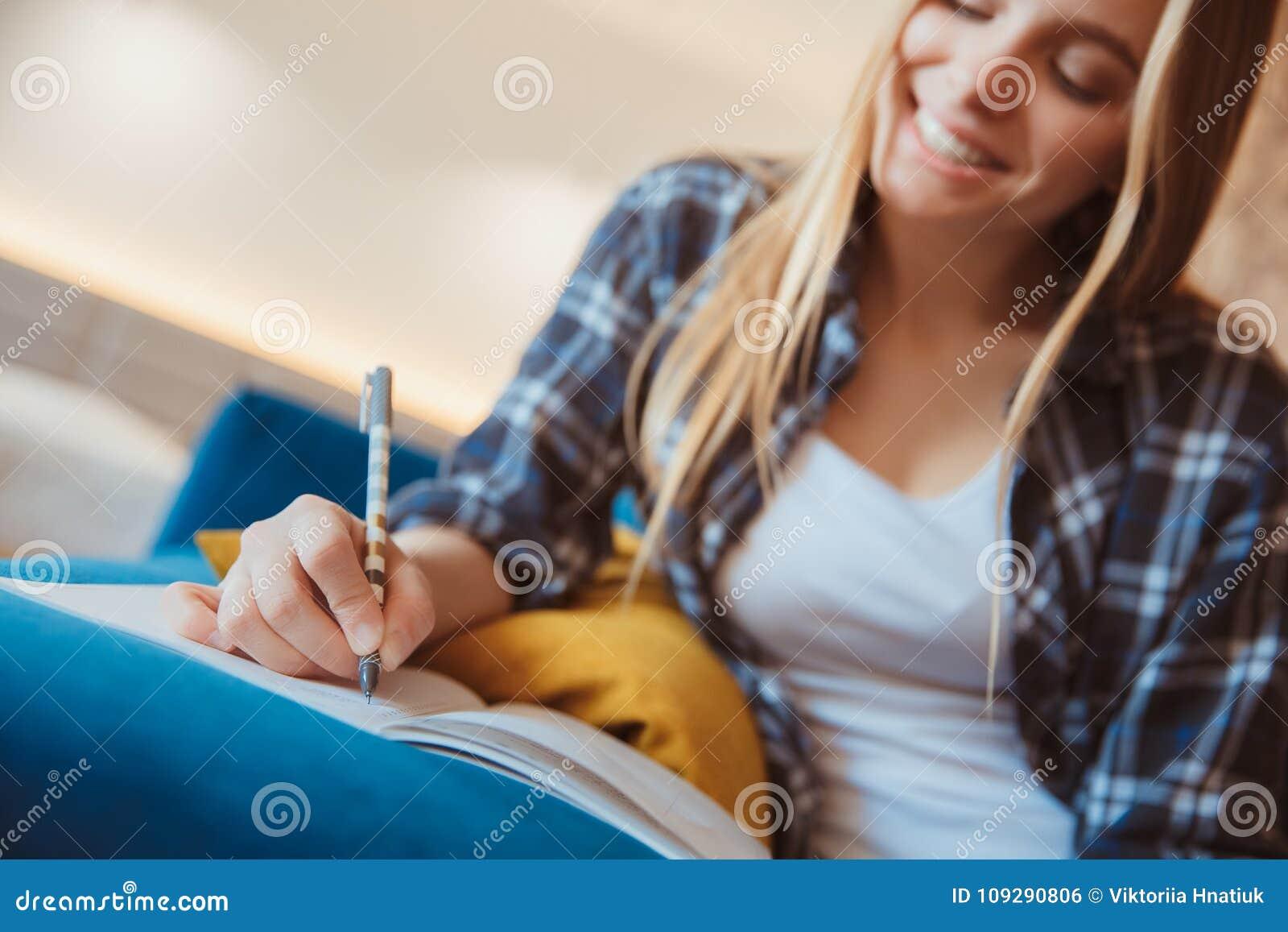 Jonge vrouw thuis in de woonkamer die nota sclose-up nemen