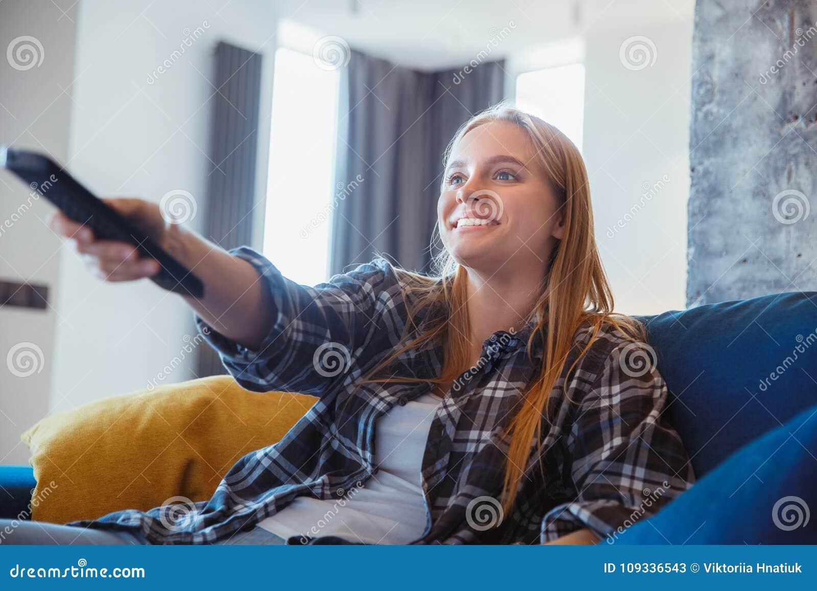 Jonge vrouw thuis in het kanaal van TV van de woonkameromschakeling