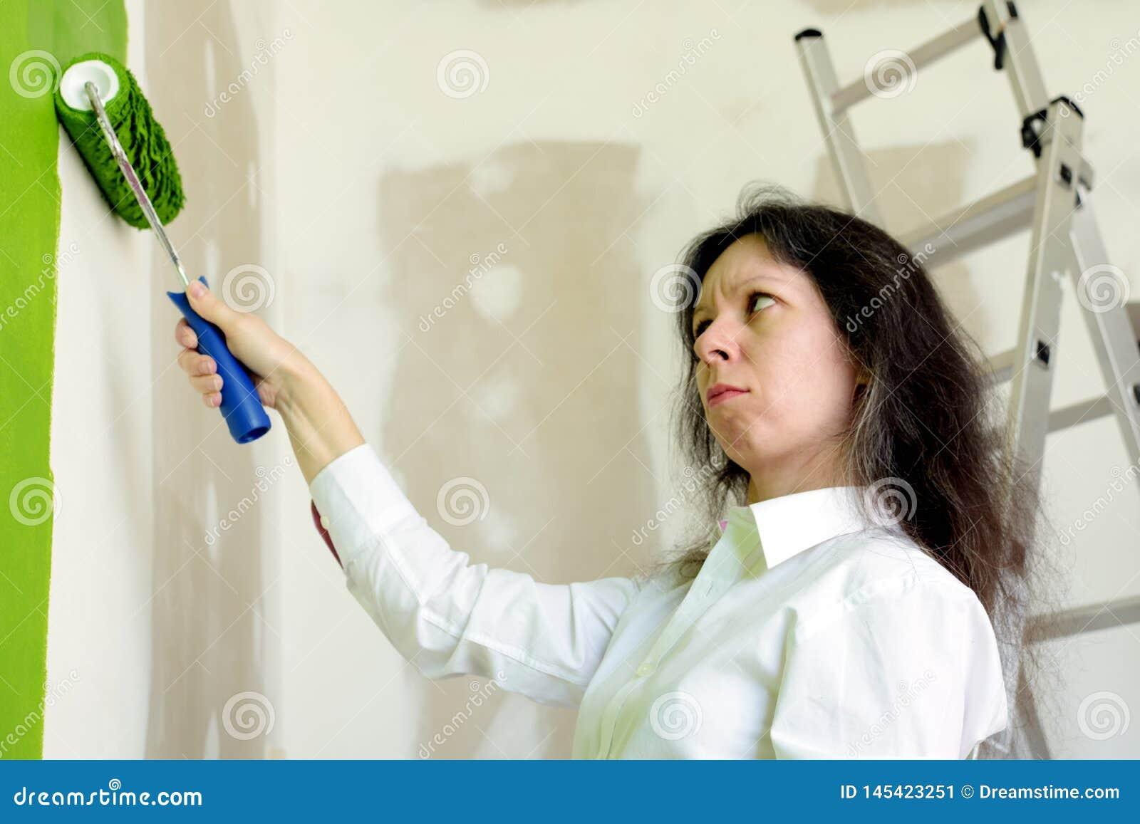 Jonge vrouw in wit die overhemd met een groene kleur van een geschilderde muur wordt verstoord