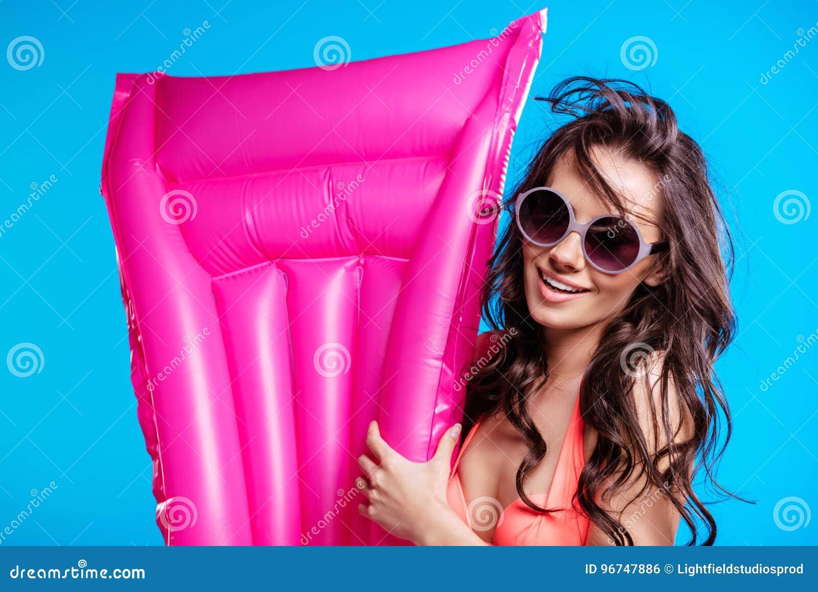 Jonge vrouw in zonnebril en de luchtmatras van de bikiniholding en het glimlachen bij camera