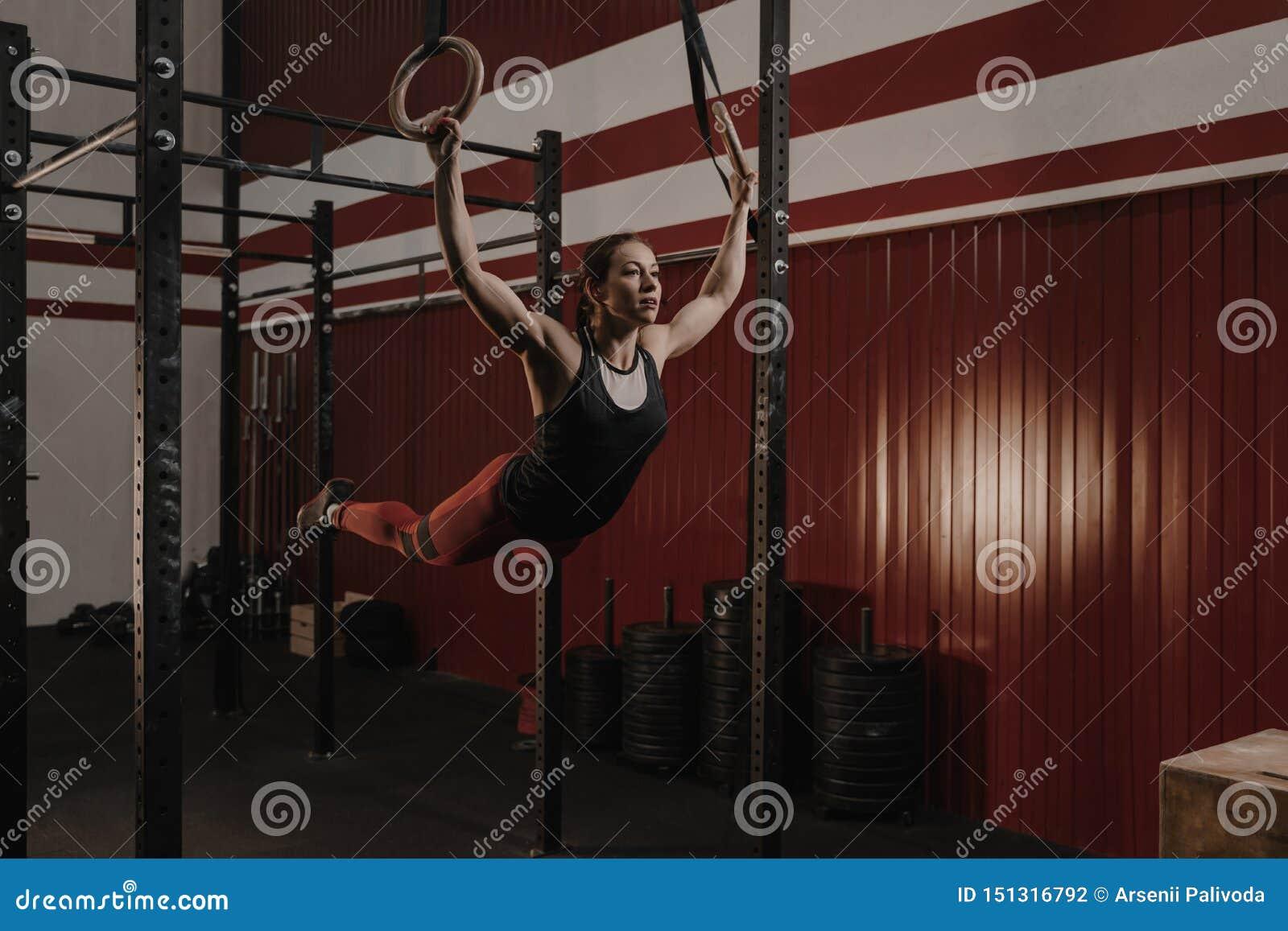 Jonge vrouwelijke atleet die op gymnastiek- ringen bij crossfitgymnastiek slingeren