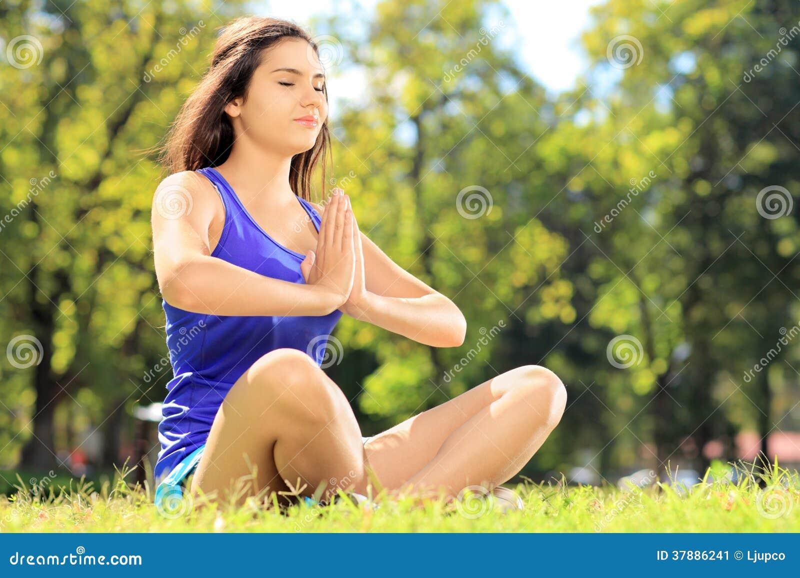 Jonge vrouwelijke atleet in sportkleding die gezette yogaoefening doen