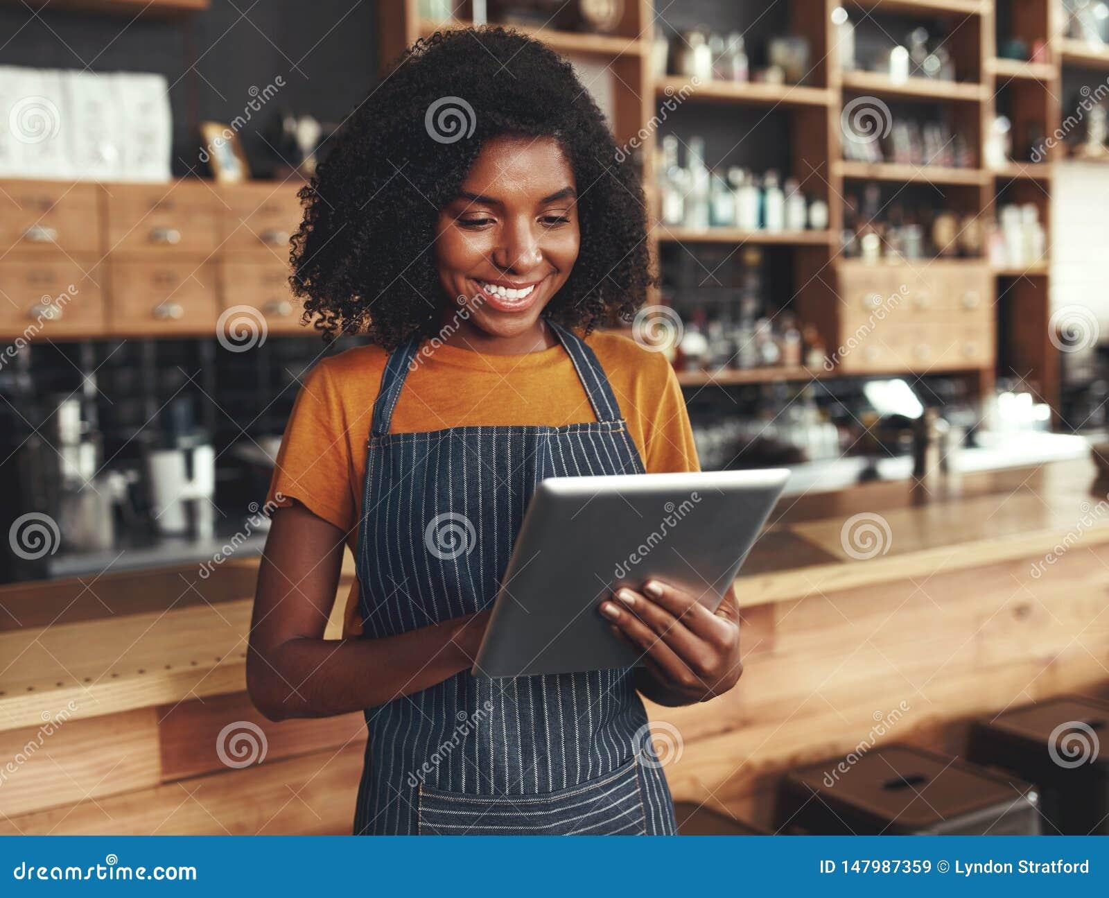 Jonge vrouwelijke eigenaar die digitale tablet gebruiken terwijl status in koffie
