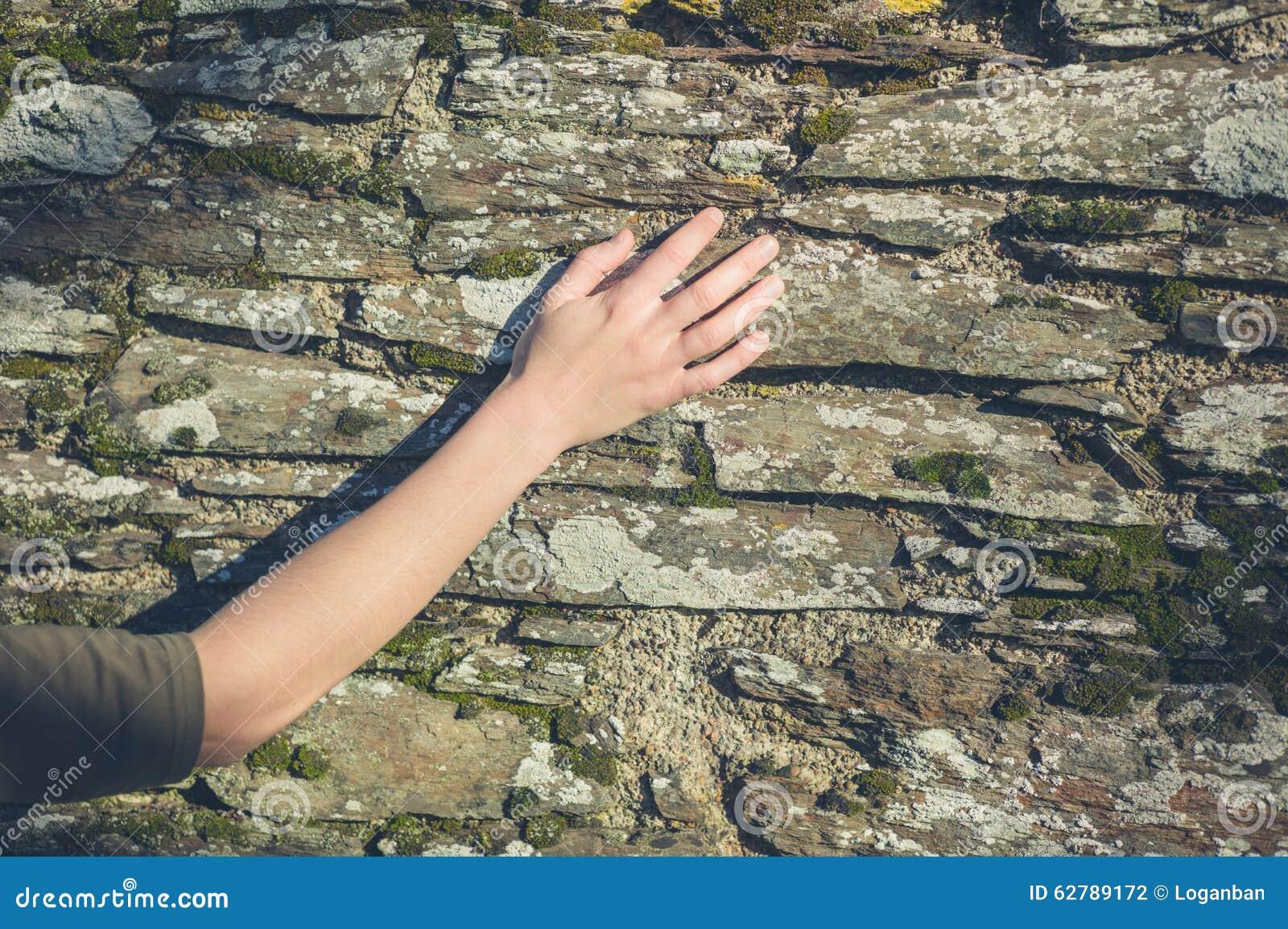 Jonge vrouwelijke hand wat betreft muur