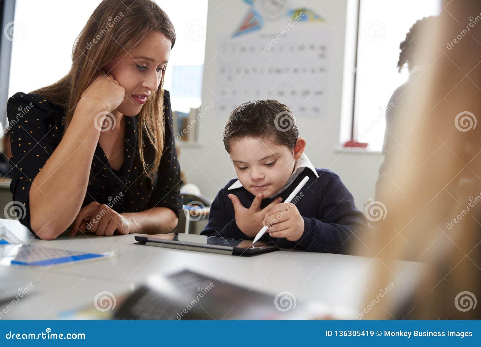 Jonge vrouwelijke leraar die met een Benedenzitting van de syndroomschooljongen bij bureau in een lage schoolklaslokaal werken, s