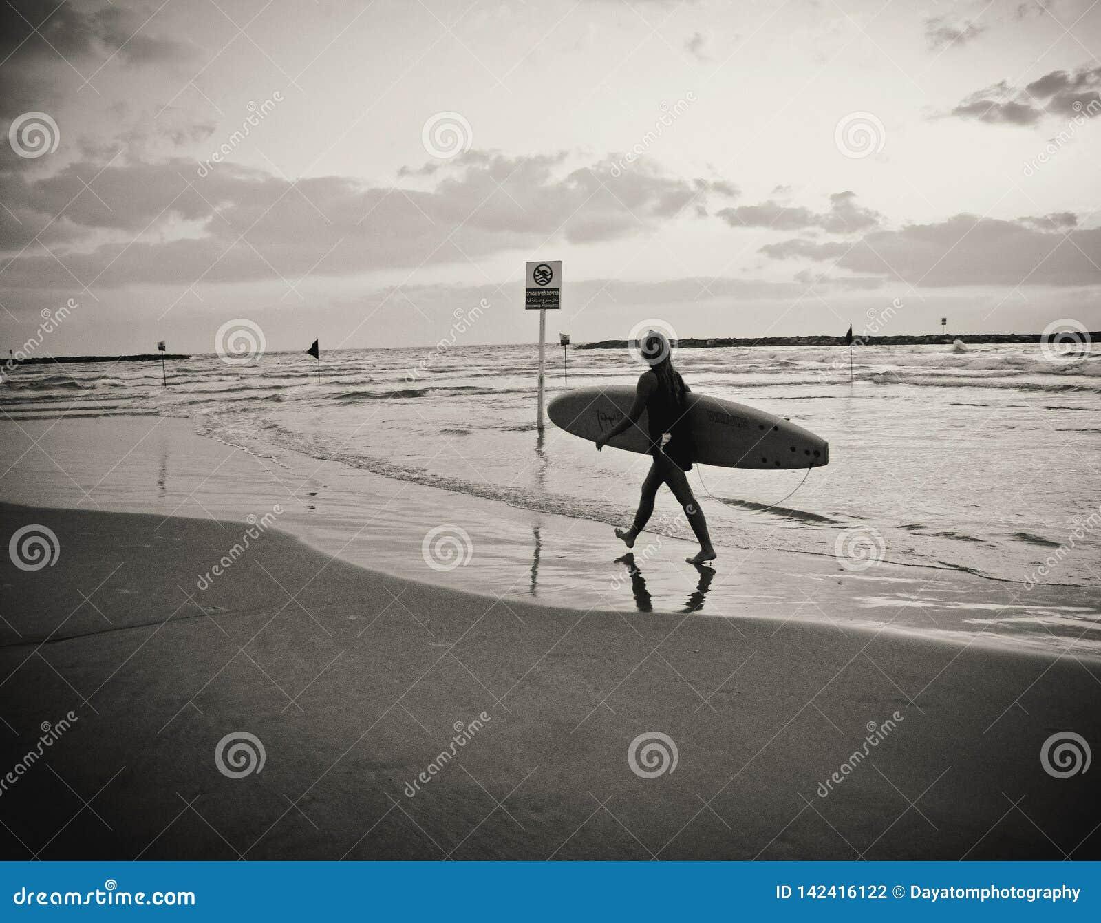 Jonge vrouwelijke surfer met raad die die op het strand lopen, water, onder een bewolkte hemel wordt overdacht