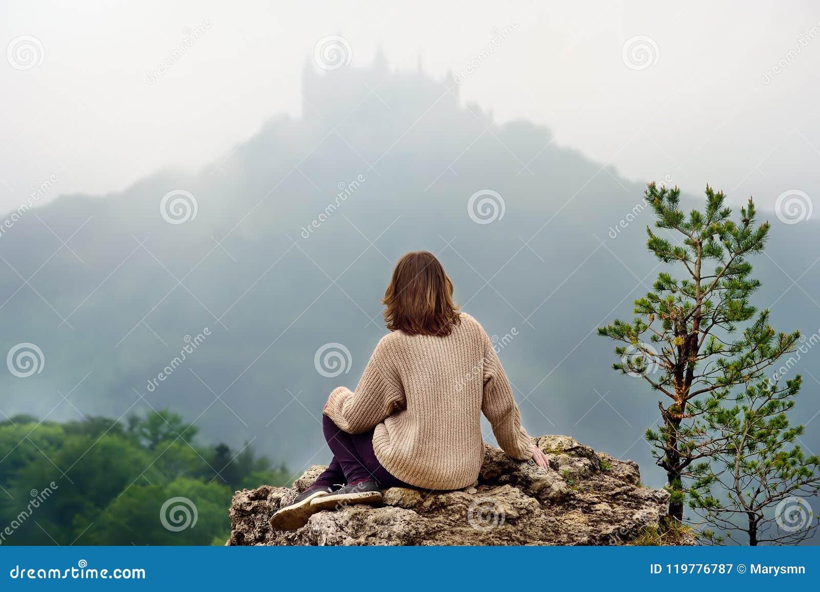 Jonge vrouwelijke toerist die op beroemd Hohenzollern-Kasteel in dikke mist, Duitsland kijken