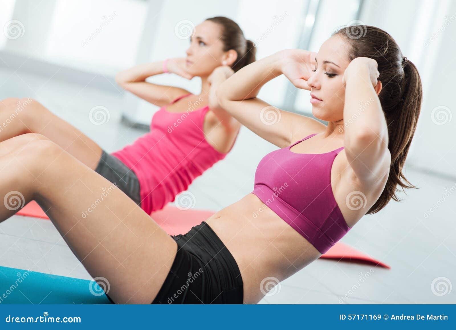 Jonge vrouwen die abs training doen bij de gymnastiek