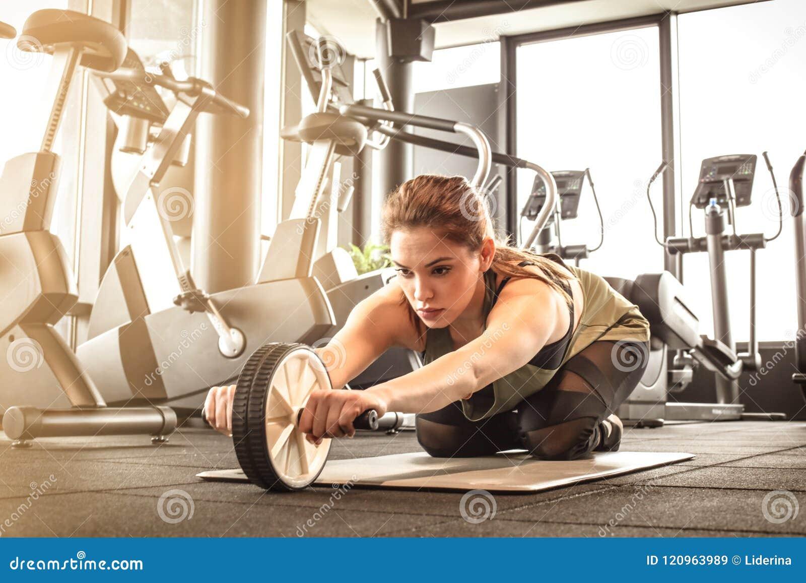 Jonge vrouwen die abs werken, die sportmateriaal met behulp van